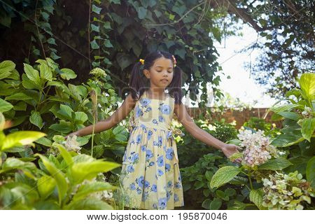 Girl standing amidst green plants in garden
