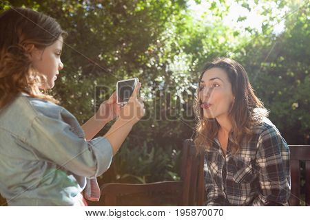 Side view of girl photographing mother sticking out tongue at backyard