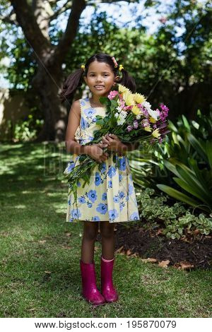 Portrait of smiling girl holding flowers bouquet standing in backyard