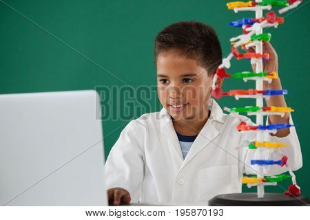 Smiling schoolboy experimenting molecule model in laboratory at school