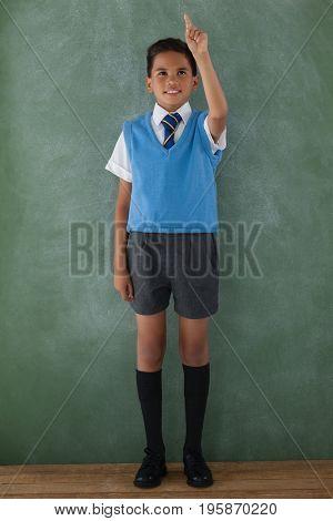 Schoolboy raising hand in classroom at school
