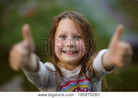Little cheerful girl showing thumbs up on nature background