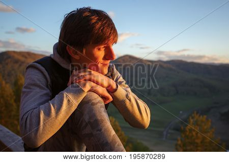 A young man, at the top of the mountain, watches the sun go down. Altai. Russia.