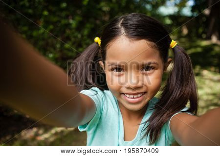 Close-up portrait of smiling girl with arms raised at backyard