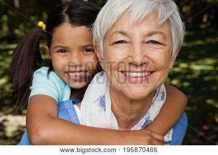 Close-up portrait of smiling grandmother giving piggyback to granddaughter at backyard