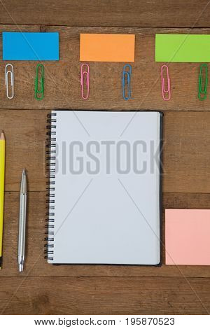 Overhead view of various school supplies on wooden table