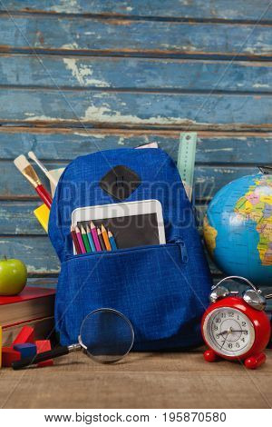 Close-up of school supplies, apple, globe, digital tablet and magnifying glass on wooden table