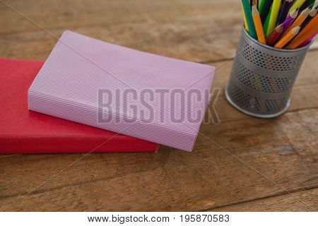 Close-up of books and color pencils on wooden table