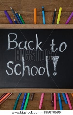 Close-up of text written on slate surrounded with school supplies