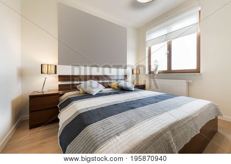 Modern bedroom in beige finishing and wooden floor