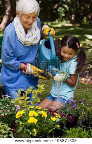 Smiling girl and grandmother watering plants in backyard