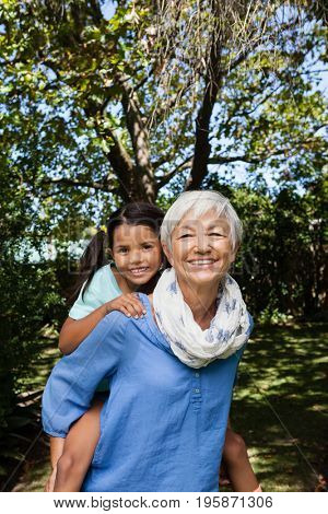 Portrait of smiling grandmother giving piggyback to granddaughter against trees at backyard