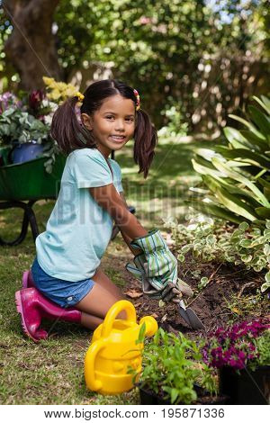 Portrait of smiling girl kneeling while digging soil with trowel at backyard