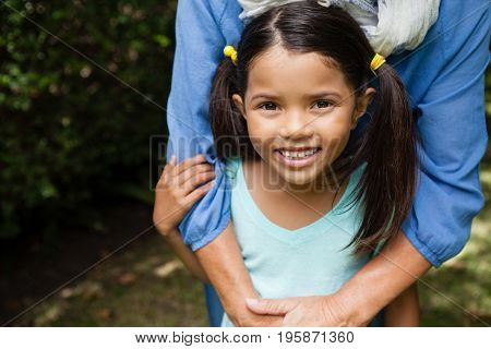 Portrait of smiling girl with grandmother standing at backyard