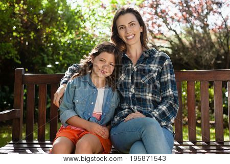 Portrait of smiling beautiful woman and daughter sitting on wooden bench at backyard