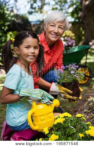 Portrait of smiling senior woman and girl watering flowers at backyard