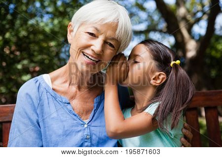 Girl whispering in ears of smiling grandmother at backyard