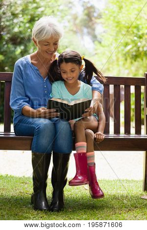 Smiling grandmother and granddaughter reading novel while sitting on wooden bench at garden