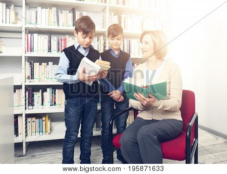 Teacher and little boys with books at school library