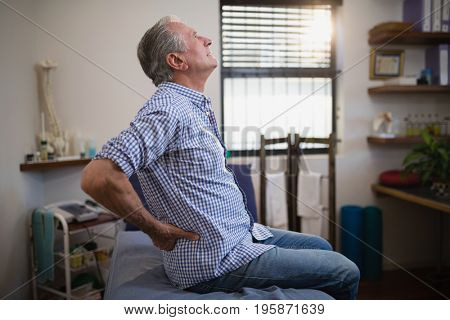 Side view of senior male patient suffering from back ache while looking up on bed at hospital ward