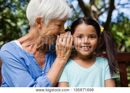 Smiling grandmother whispering in ears of girl at backyard