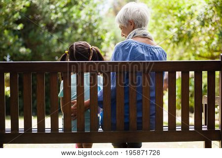 Rear view of granddaughter and grandmother sitting on wooden bench at backyard