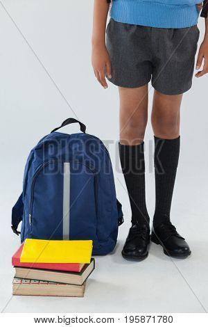 Low-section of schoolboy standing with school bag and books on white background