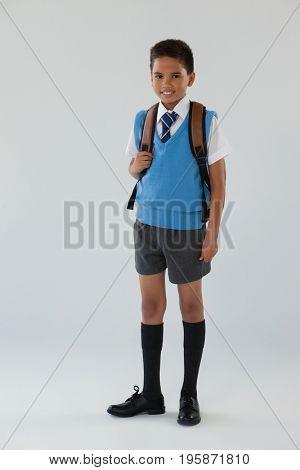 Portrait of schoolboy in school uniform with school bag on white background
