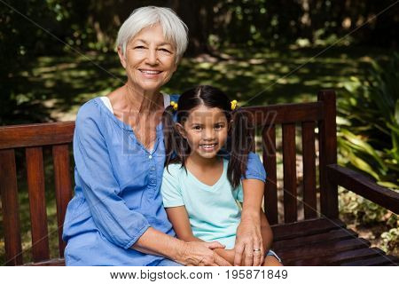 Portrait of senior woman with granddaughter sitting on wooden bench at backyard