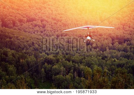 paraglider with a motor on the background of mountains and forests, in the setting sun, moves to the camera. The concept of extreme rest in the air.