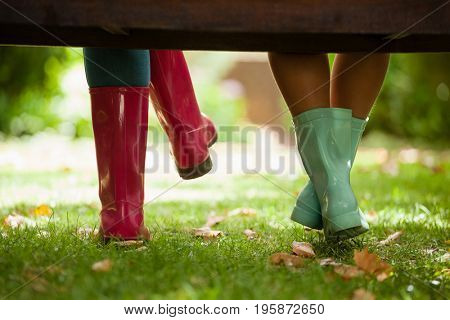 Low section of woman and daughter sitting on wooden bench at backyard