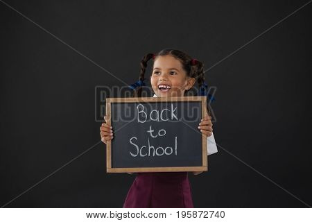 Smiling schoolgirl holding slate with text against blackboard in classroom
