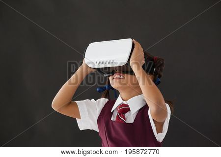 Schoolgirl using virtual reality headset against blackboard in classroom