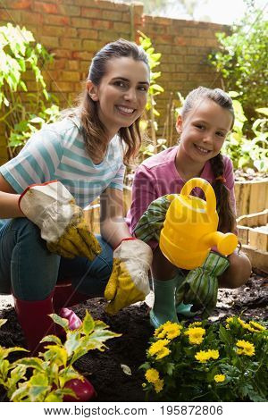 Portrait of smiling woman and daughter crouching by flowers with watering can at backyard