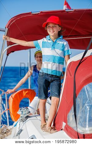 Boy captain with his sister on board of sailing yacht on summer cruise. Travel adventure, yachting with child on family vacation. Kid clothing in sailor style, nautical fashion.