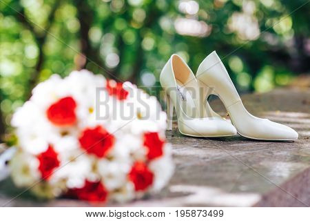 Beautiful wedding shoes and a bridal bouquet.