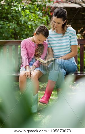 Girl sitting with mother reading novel on wooden bench at backyard