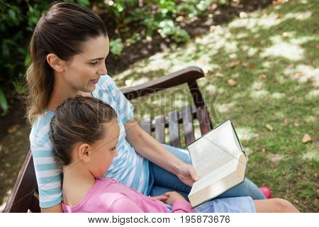 Tilt shot of mother reading novel to daughter on wooden bench at garden