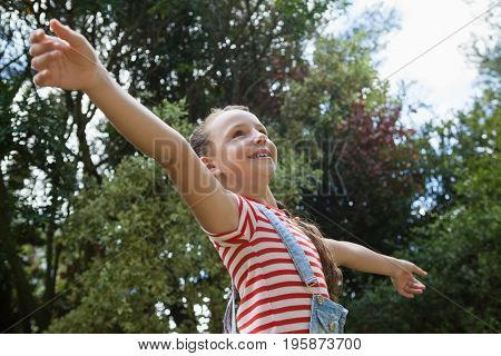 Low angle view of smiling girl with arms outstretched standing against trees at backyard