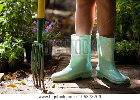 Low section of girl wearing green rubber boot standing with gardening fork on footpath at backyard