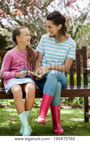 Smiling mother and daughter reading novel while sitting on wooden bench at backyard