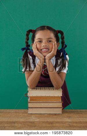 Portrait of schoolgirl leaning on books stack against chalkboard in classroom