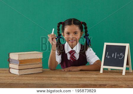 Schoolgirl calculating sums at desk against chalkboard