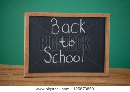 Slate with text back to school on table against green background