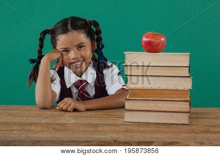 Portrait of schoolgirl sitting beside books stack with apple on top against chalkboard