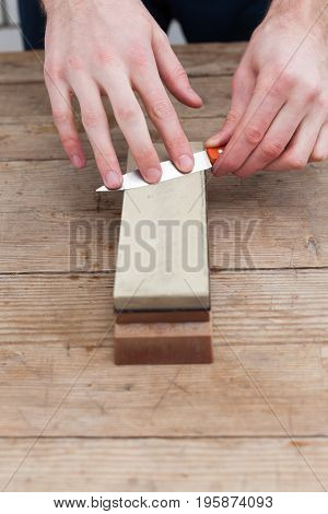 Sharpening the knife with a whetstone on a wooden background. Top view