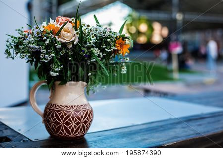 bouquet of colorful flowers in a vase decorate an outdoor balcony