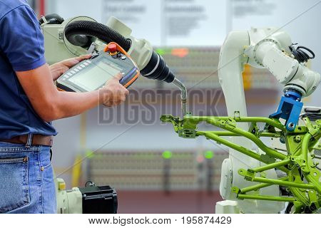 Engineers use a wireless remote control of robotic welding and robot workpiece for smart factory, industry 4.0 concept