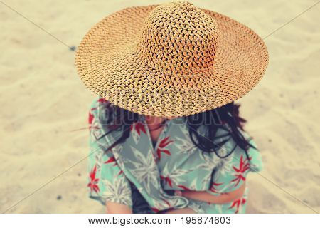 Woman in straw hat on the beach