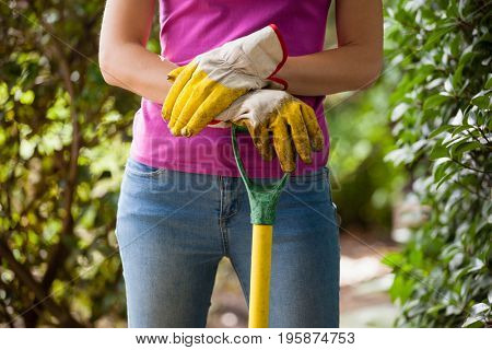 Midsection of woman holding gardening fork standing amidst plants at backyard